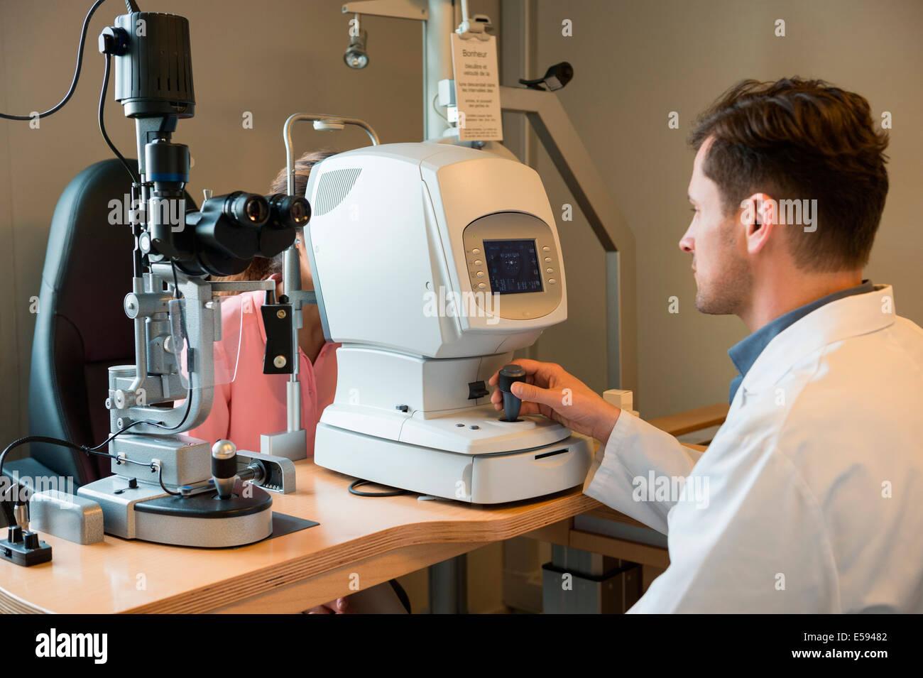 Male optometrist examining woman's eyes Stock Photo