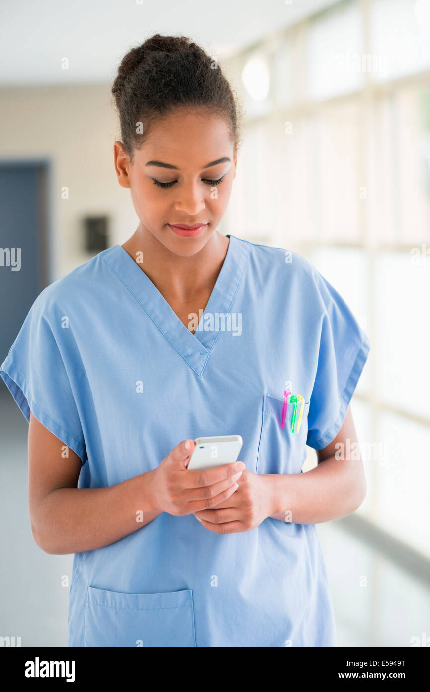Female nurse text messaging with a mobile phone - Stock Image
