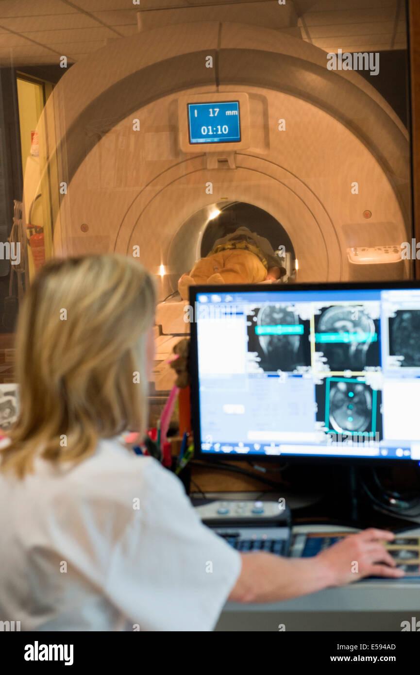 Female doctor examining brain MRI scan on computer - Stock Image