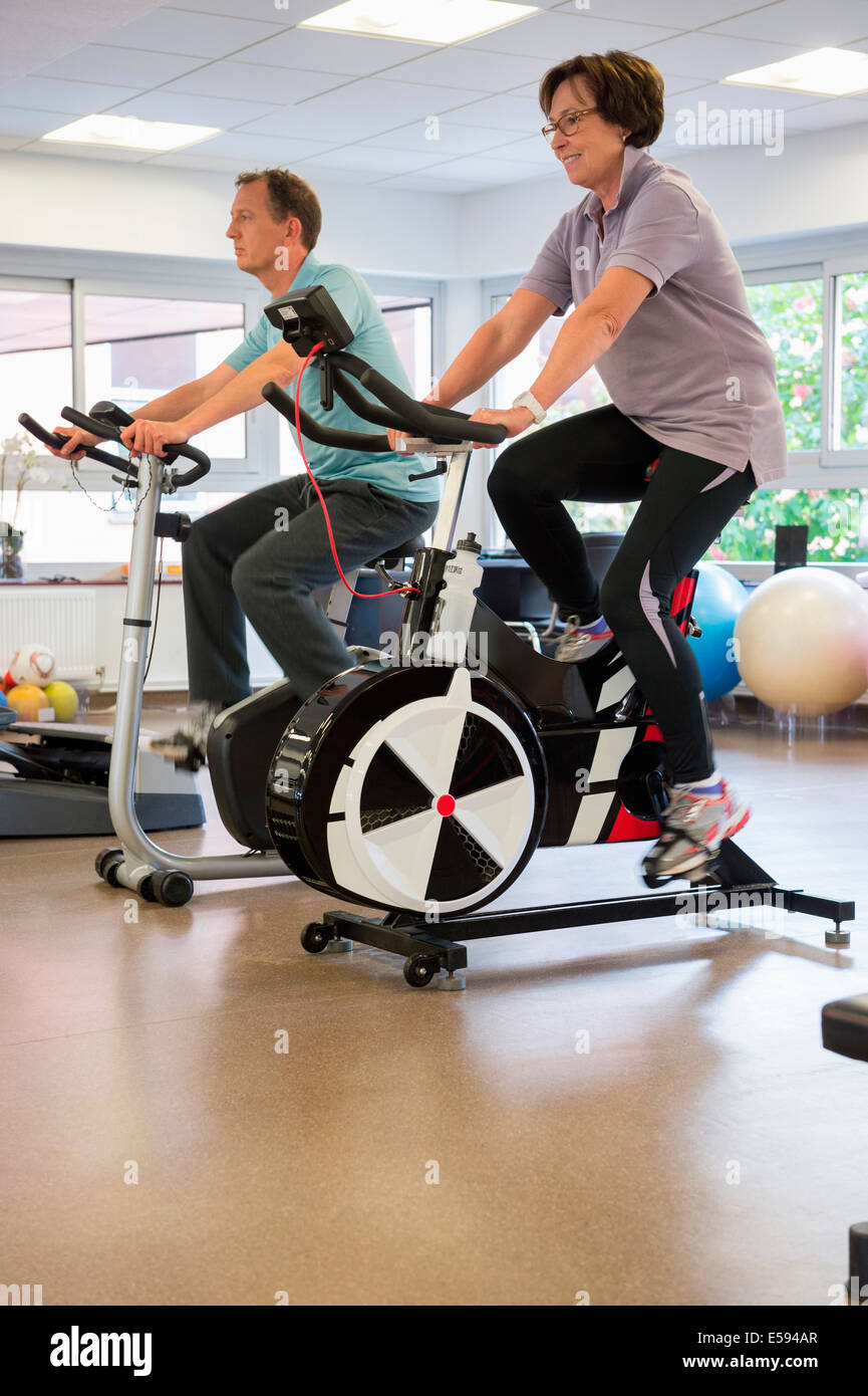 Man and woman in a spinning class at the gym - Stock Image