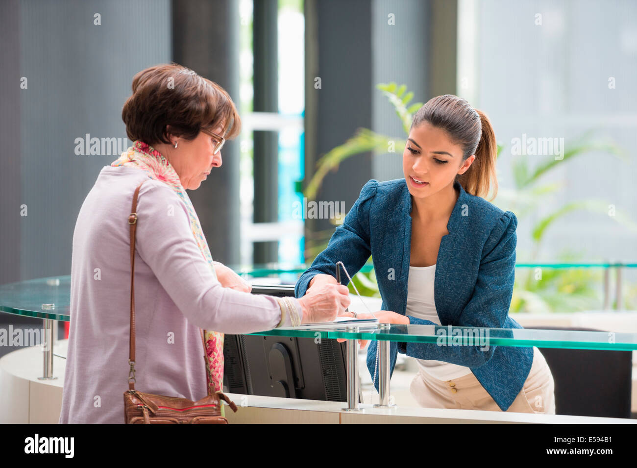Woman signing paper at reception desk - Stock Image