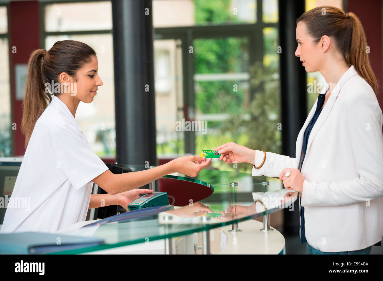 Woman giving french social security card to receptionist at hospital reception desk - Stock Image