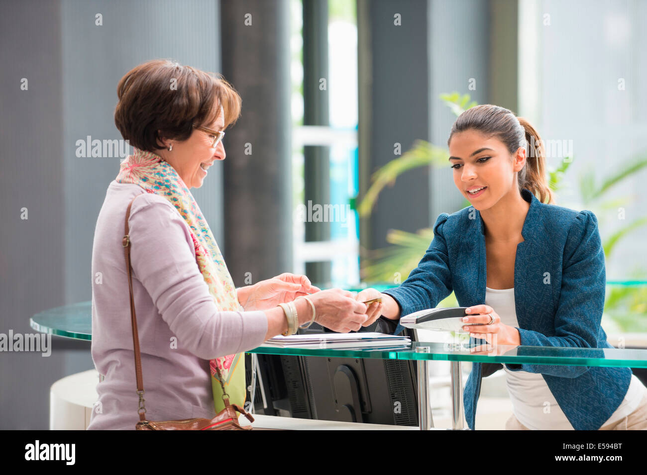 Woman making payment with credit card at reception desk - Stock Image