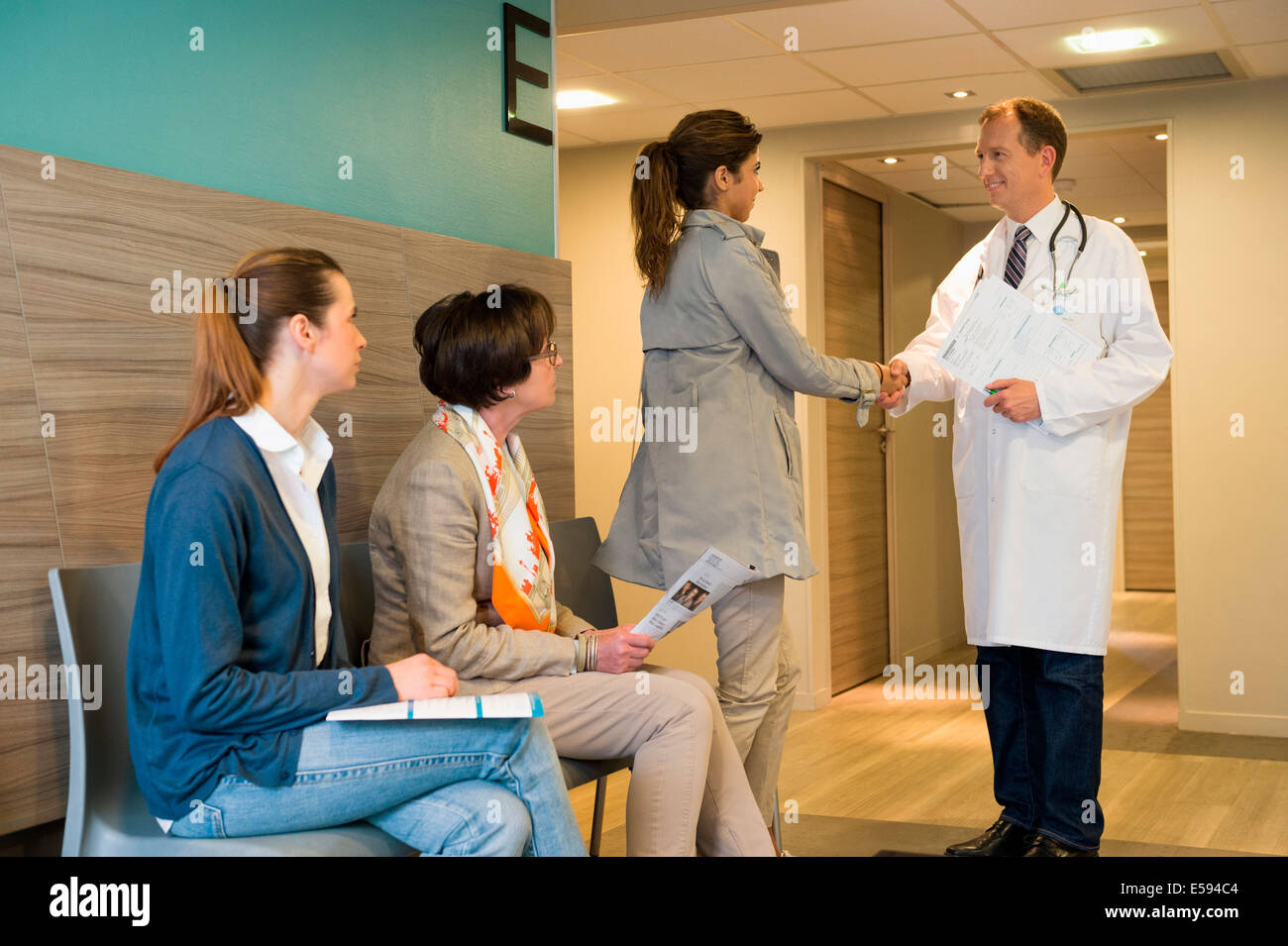 Male doctor shaking hands with his patient in waiting room - Stock Image