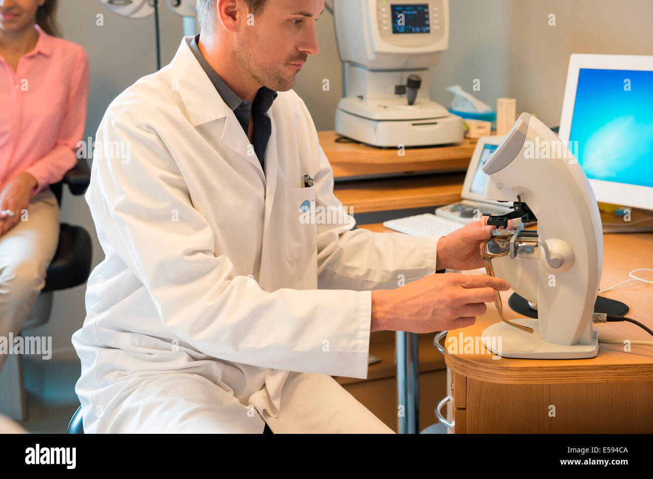 Male optometrist examining eye test equipment - Stock Image