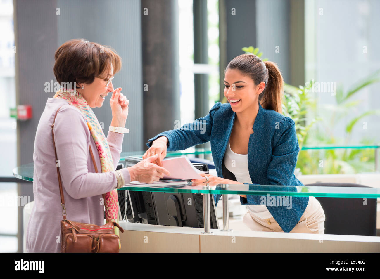 Female receptionist handing papers to a woman at reception desk - Stock Image