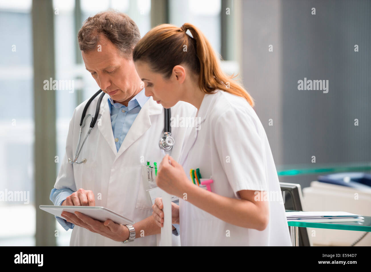 Two doctors analyzing medical report on digital tablet in hospital - Stock Image
