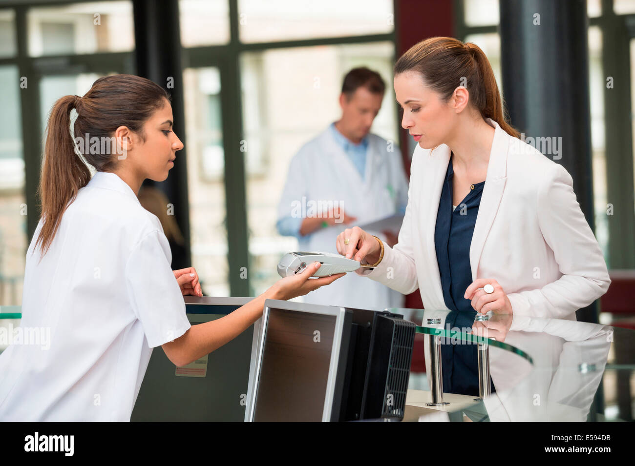 Female doctor making payment with credit card at hospital reception desk - Stock Image