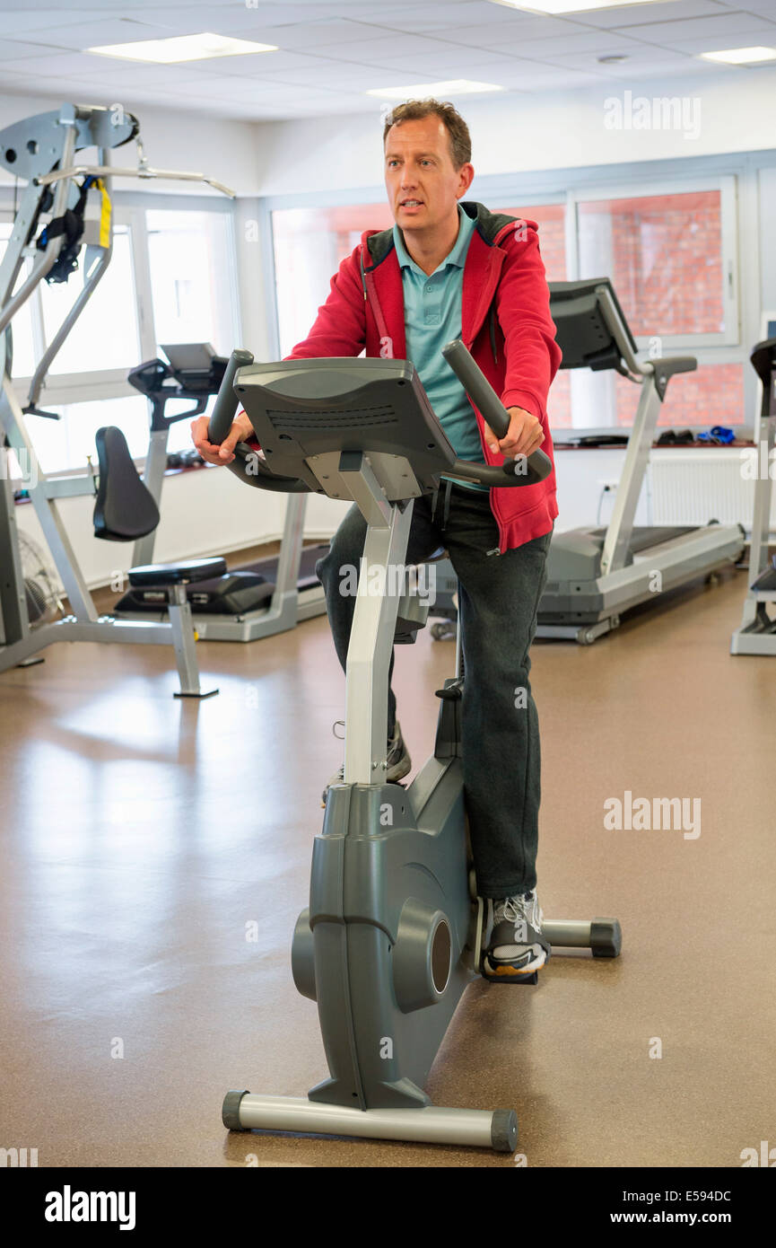Man exercising on exercise bike in a gym - Stock Image