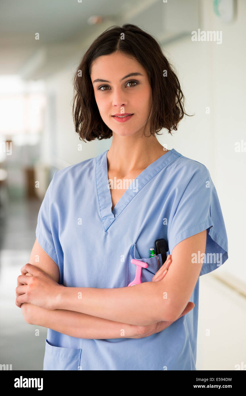 Portrait of a female nurse standing with her arms crossed - Stock Image