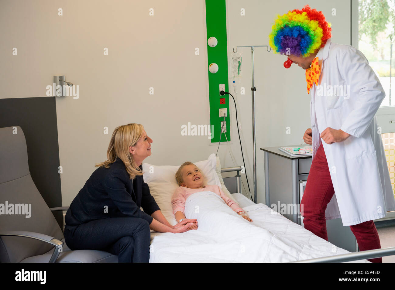 Male doctor wearing clown costume making girl patient laugh in hospital bed Stock Photo