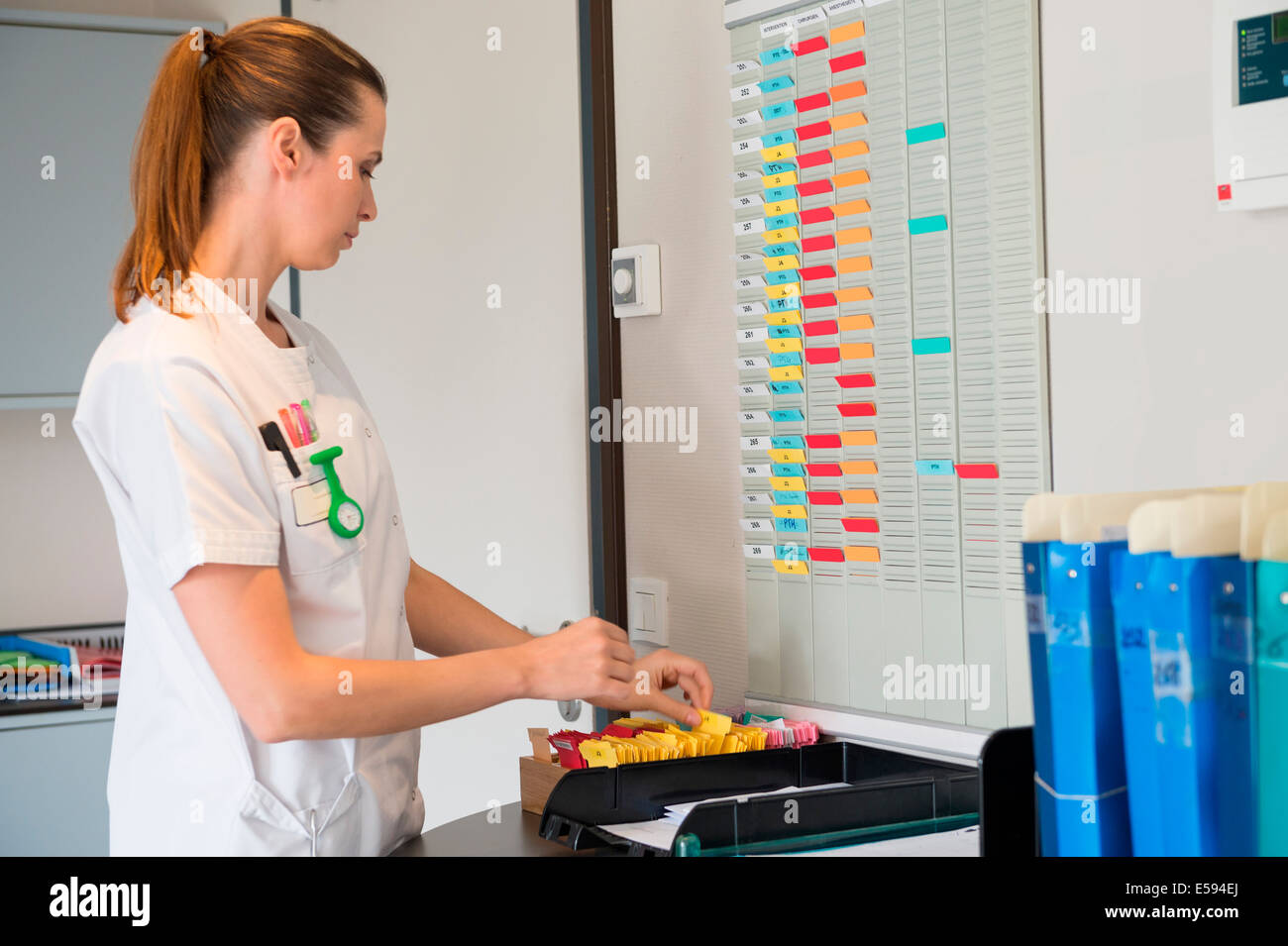 Female nurse arranging schedule in hospital - Stock Image