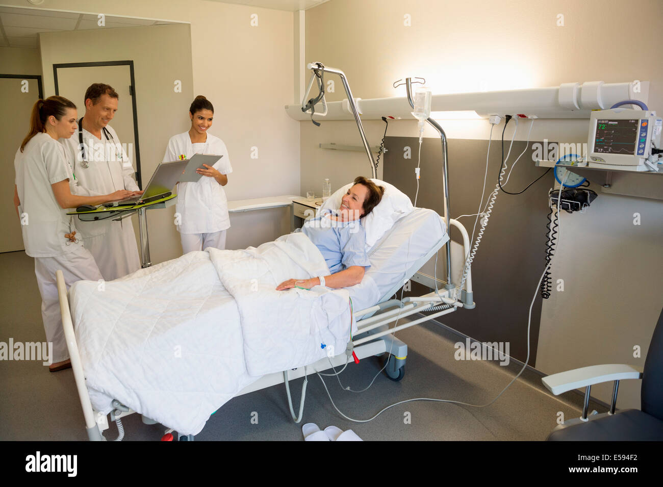 Medical team attending female patient on hospital bed - Stock Image