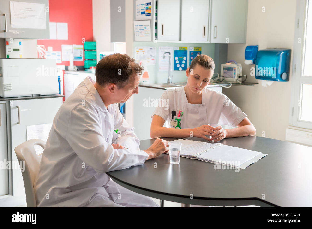 Doctor and nurse analyzing medical record in a hospital - Stock Image