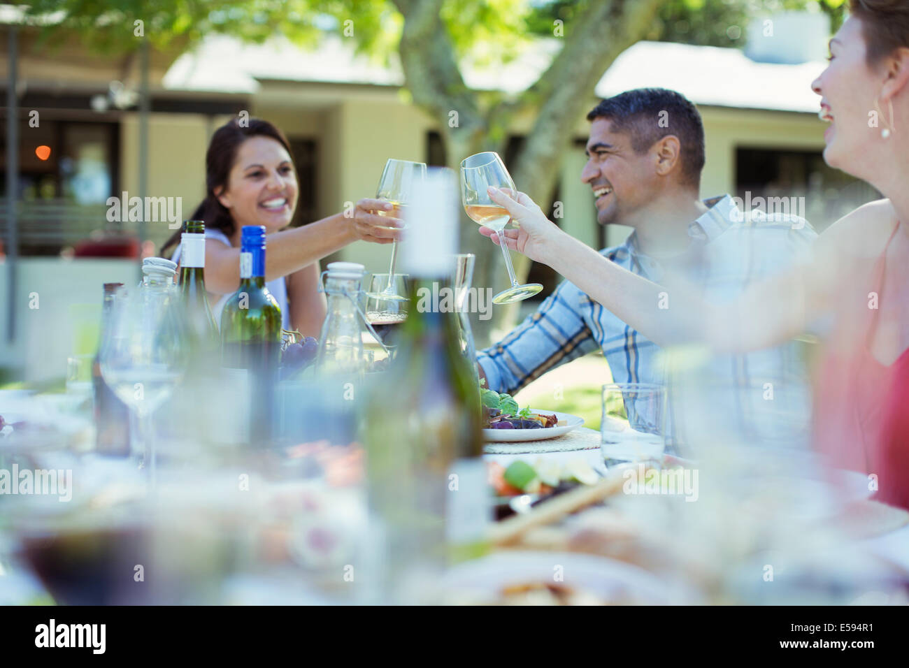 Friends toasting each other at dinner outdoors - Stock Image