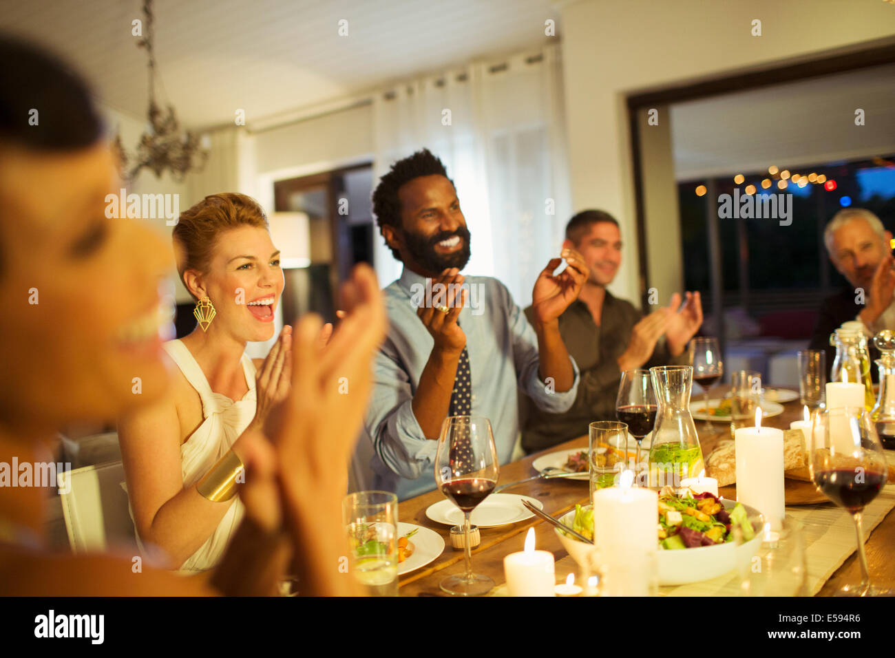 Friends cheering at dinner party - Stock Image