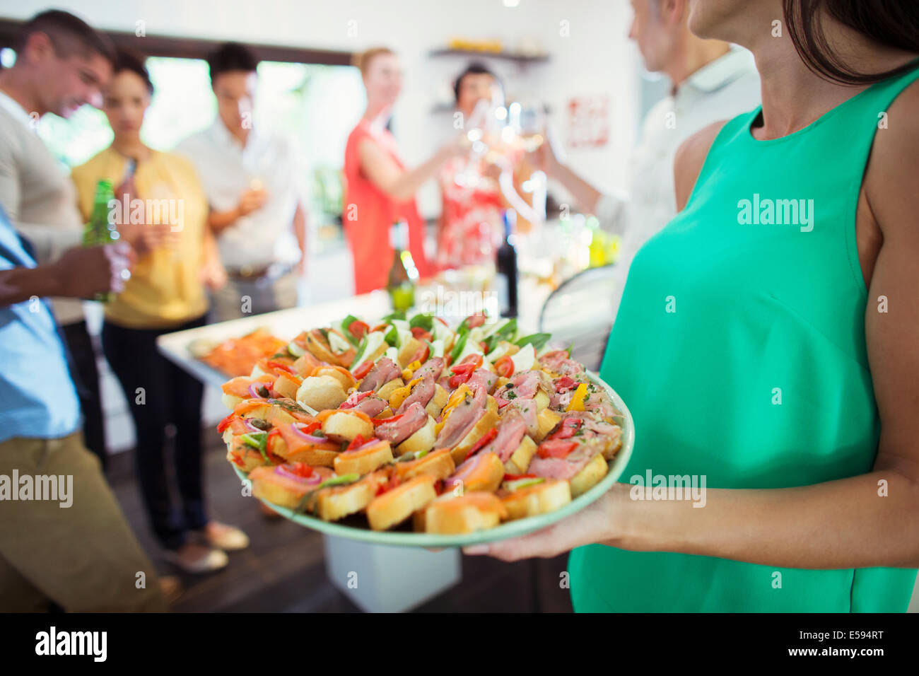 Woman serving tray of food at party - Stock Image