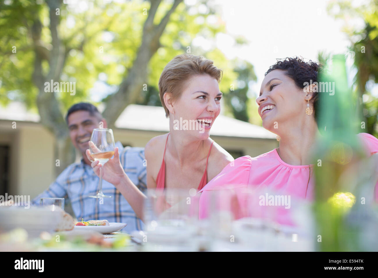 Women talking at table outdoors - Stock Image