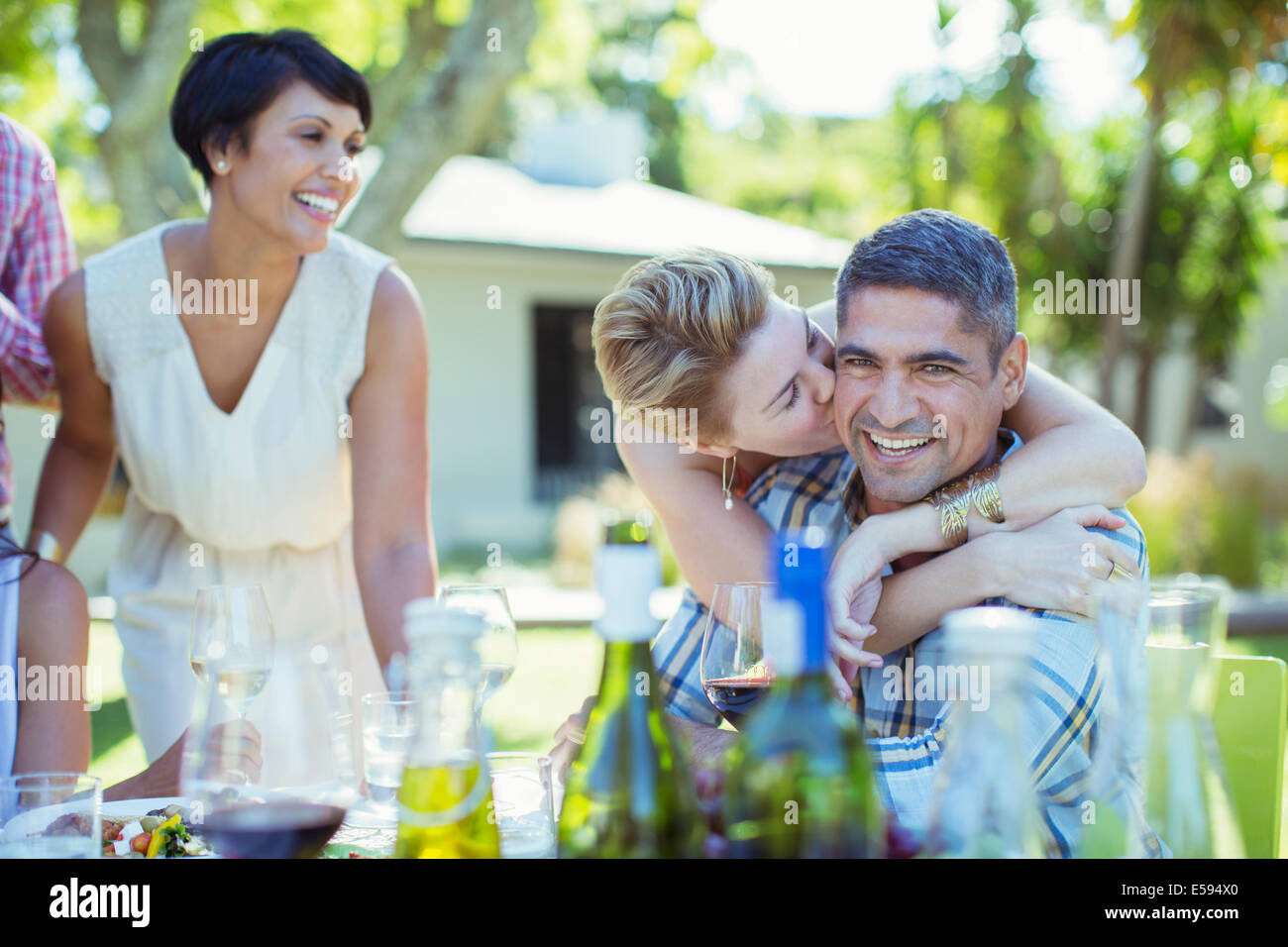 Couple kissing at table outdoors - Stock Image