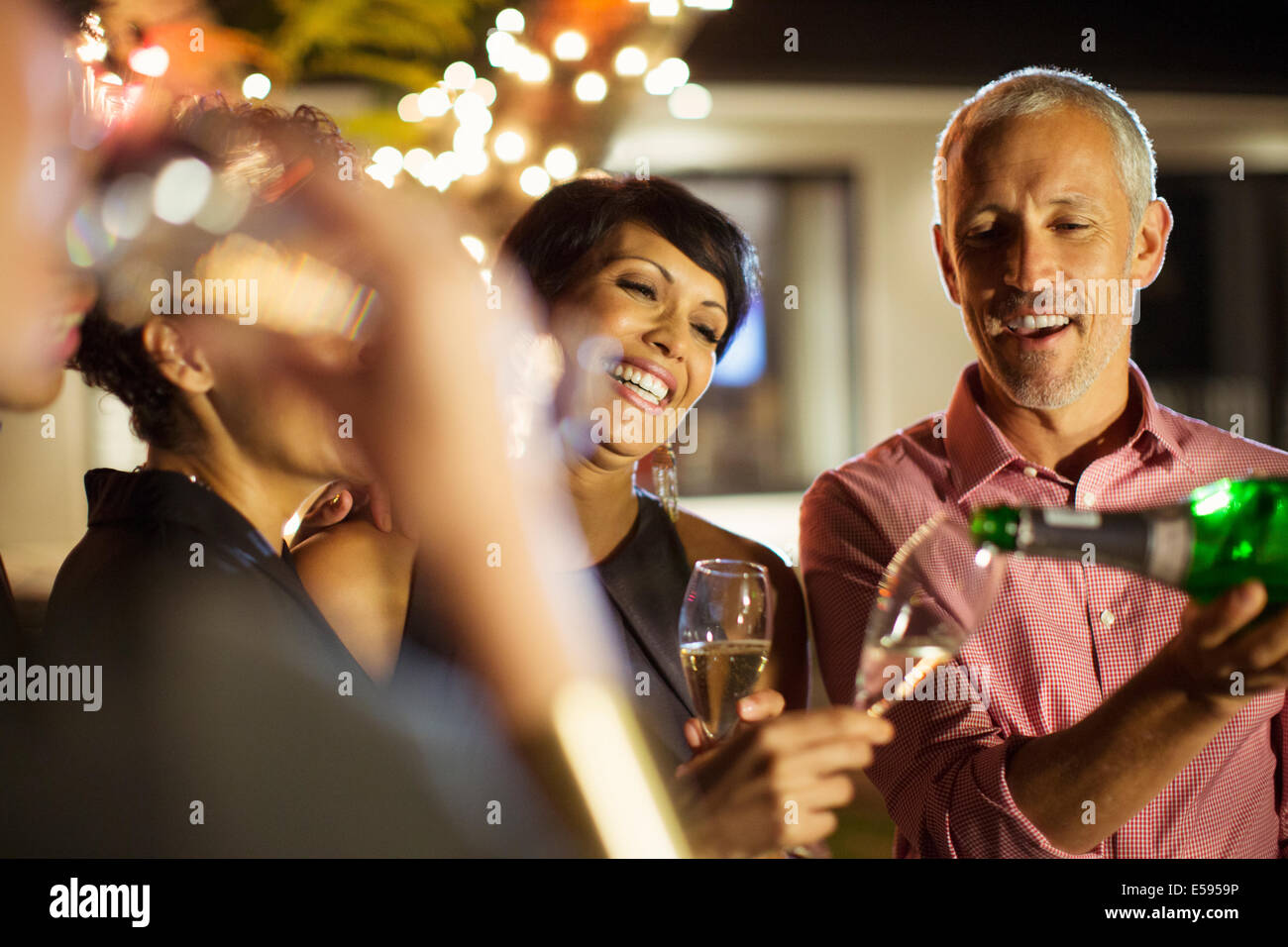 Friends drinking champagne at party - Stock Image