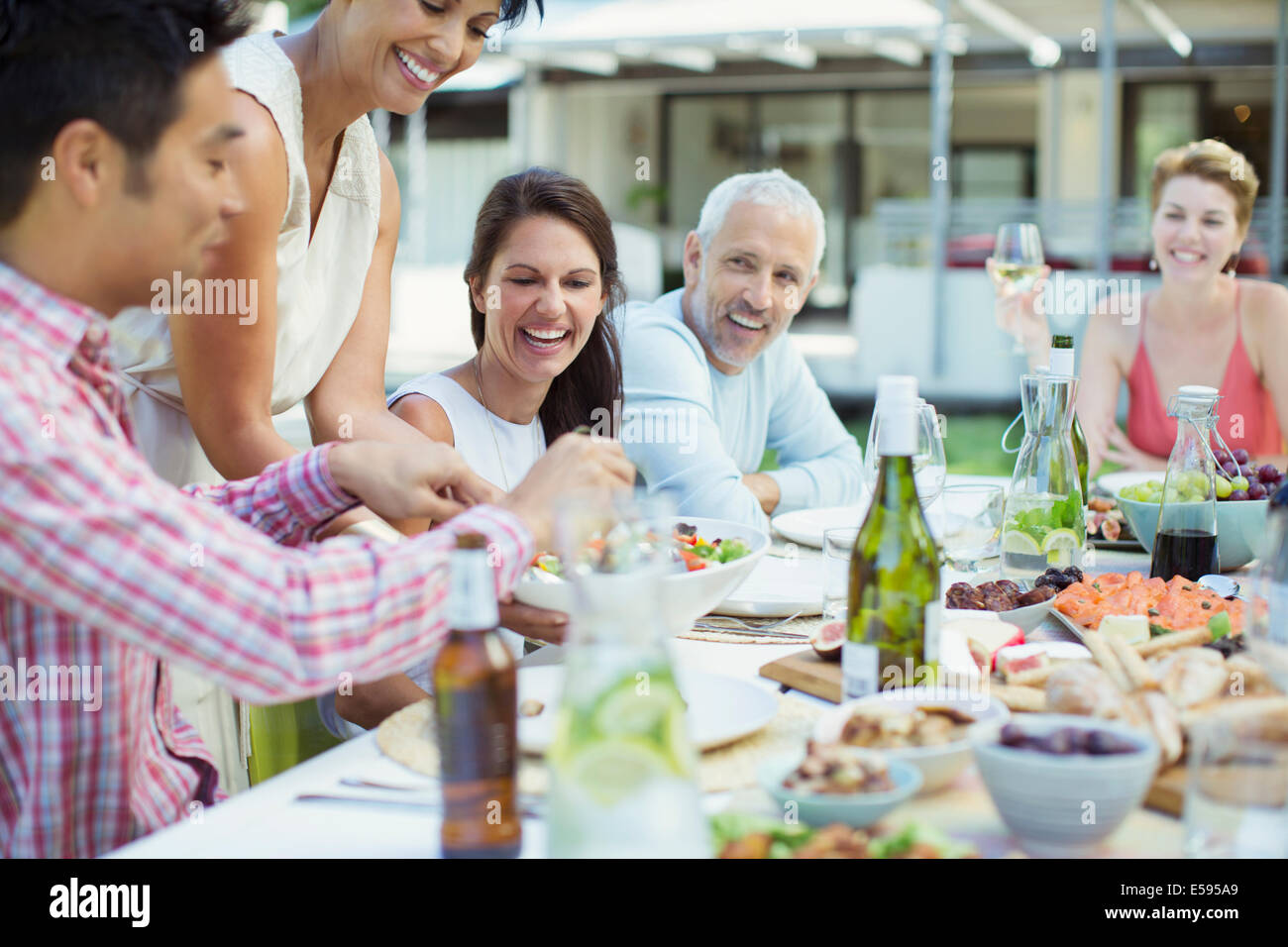 Woman serving friends at party - Stock Image