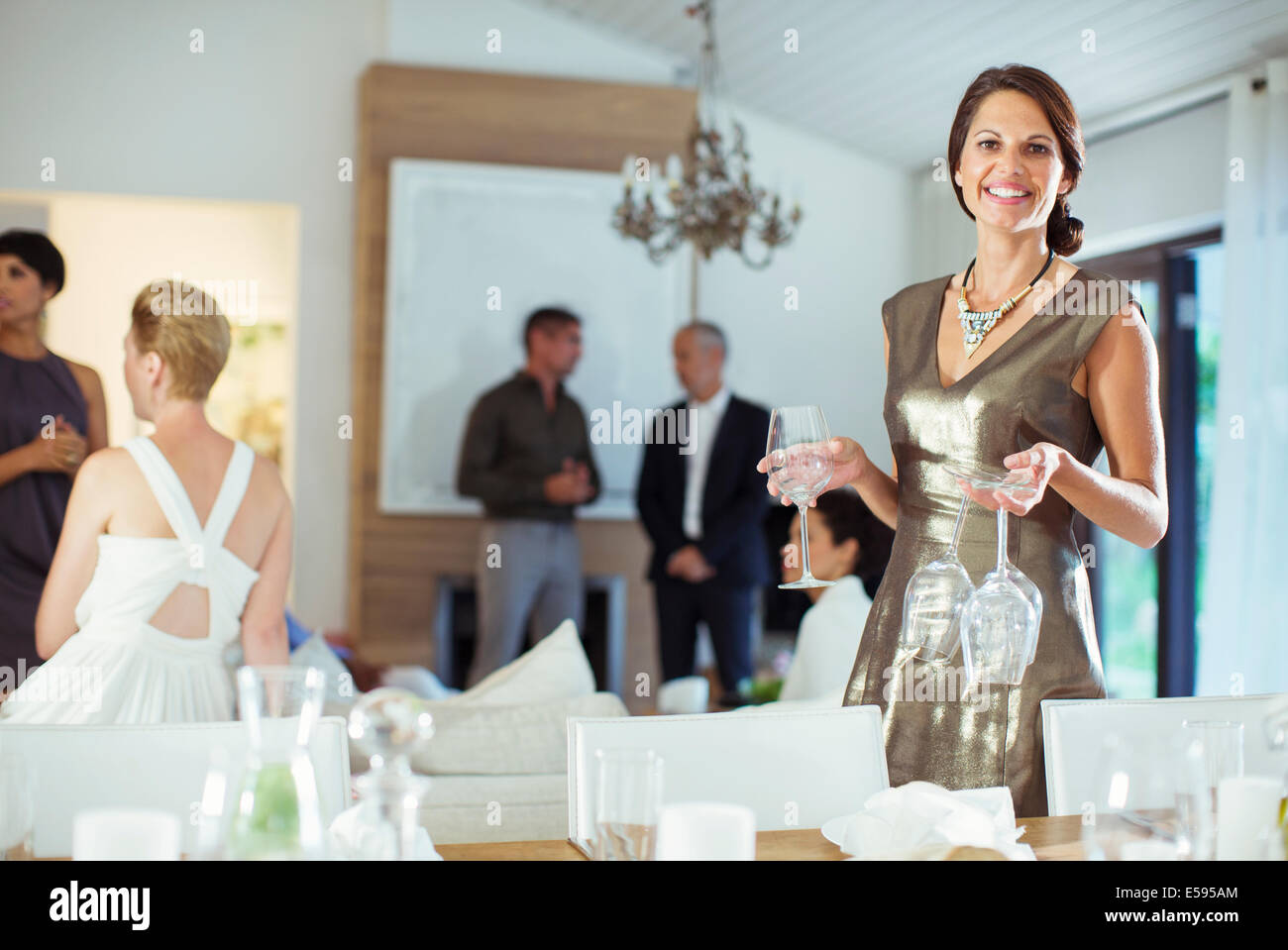Woman setting table at dinner party - Stock Image