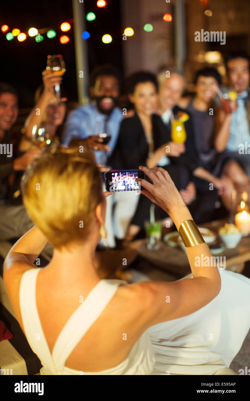 Woman taking picture of friends at party - Stock Image