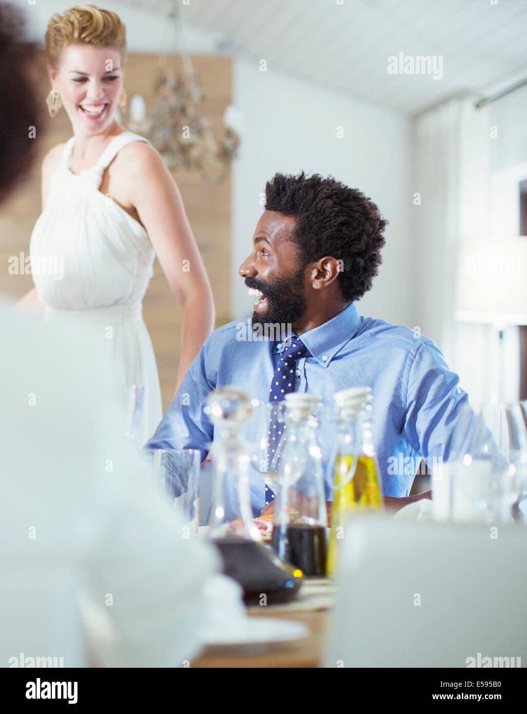 Man laughing at dinner party - Stock Image