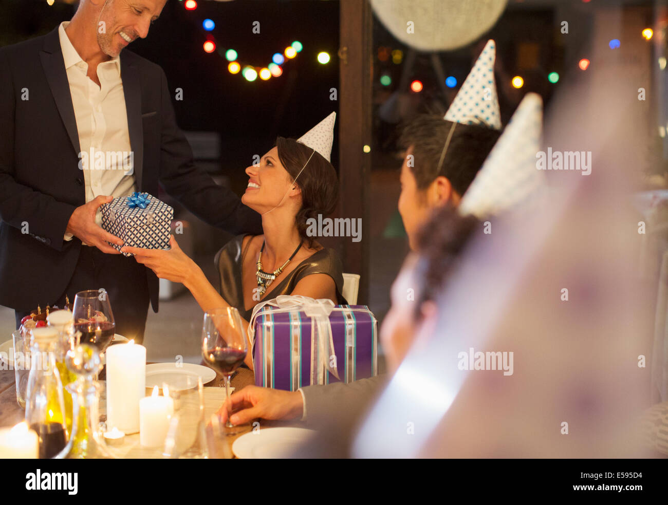 Man giving present at birthday party - Stock Image