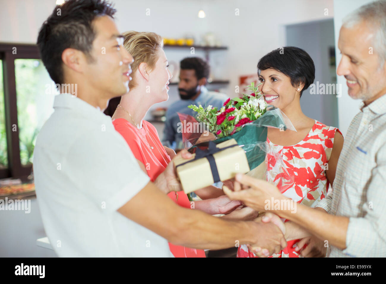 Couple exchanging gifts at party - Stock Image