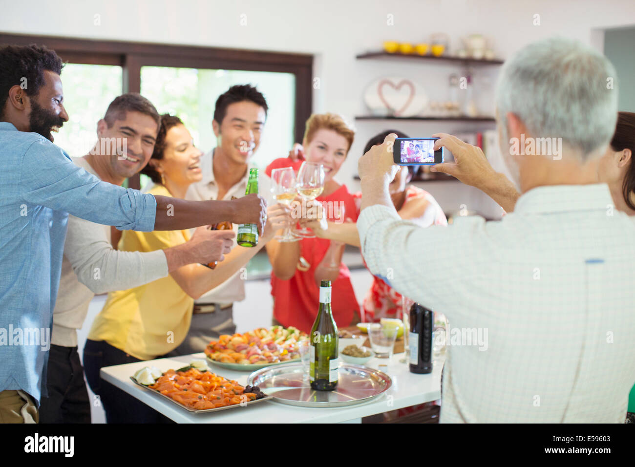 Man taking picture of friends at party - Stock Image