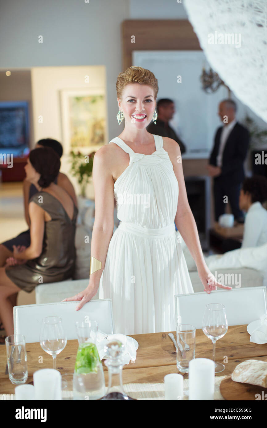 Woman standing at table at party - Stock Image