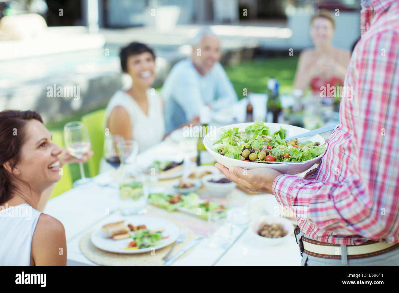 Man serving friends at table outdoors - Stock Image