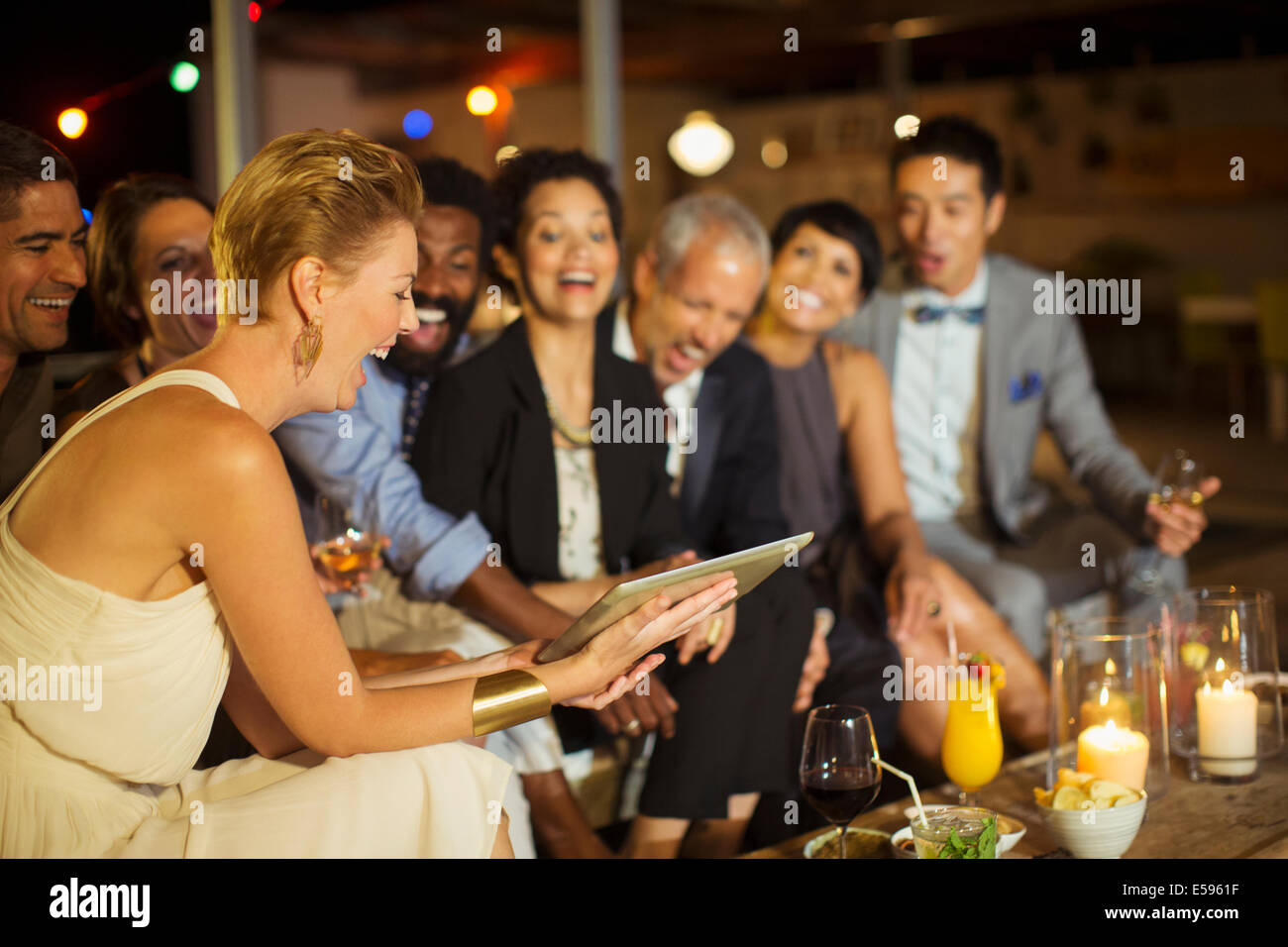 Friends using digital tablet at party - Stock Image