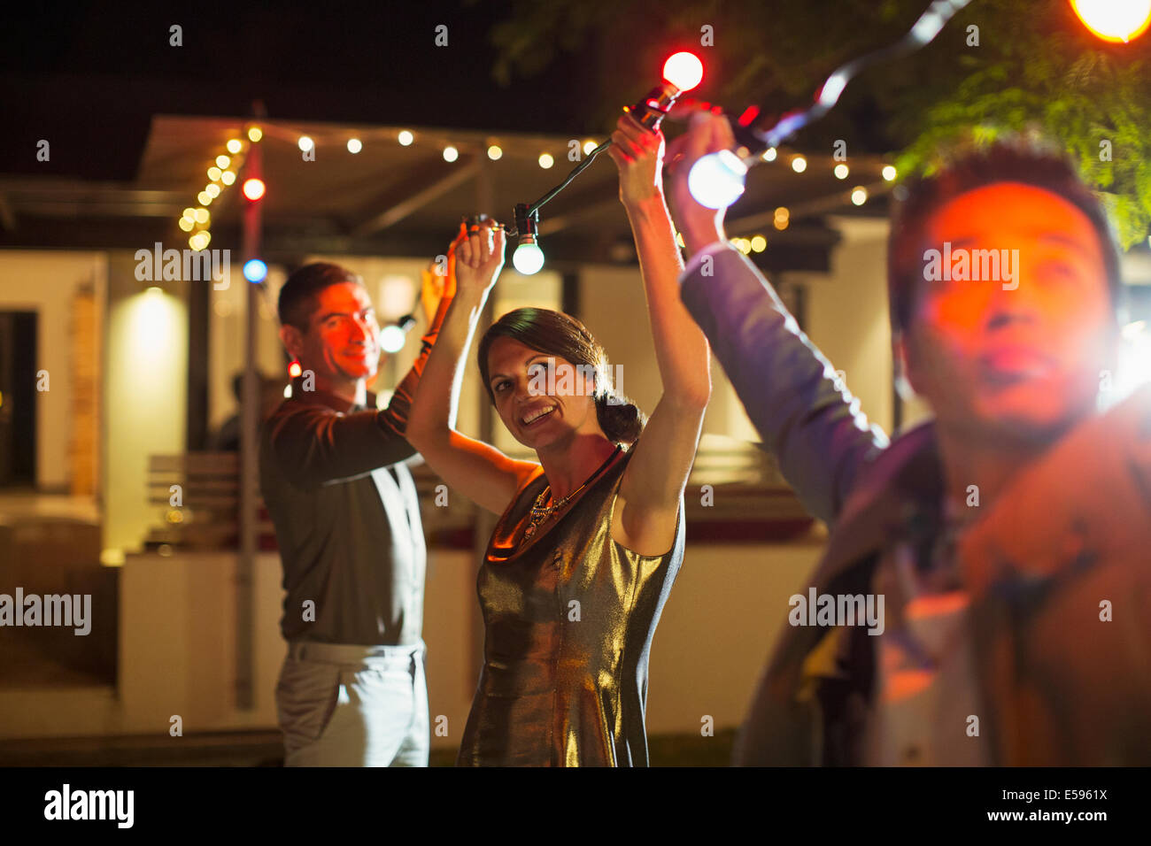 Friends stringing lights at outdoor party - Stock Image