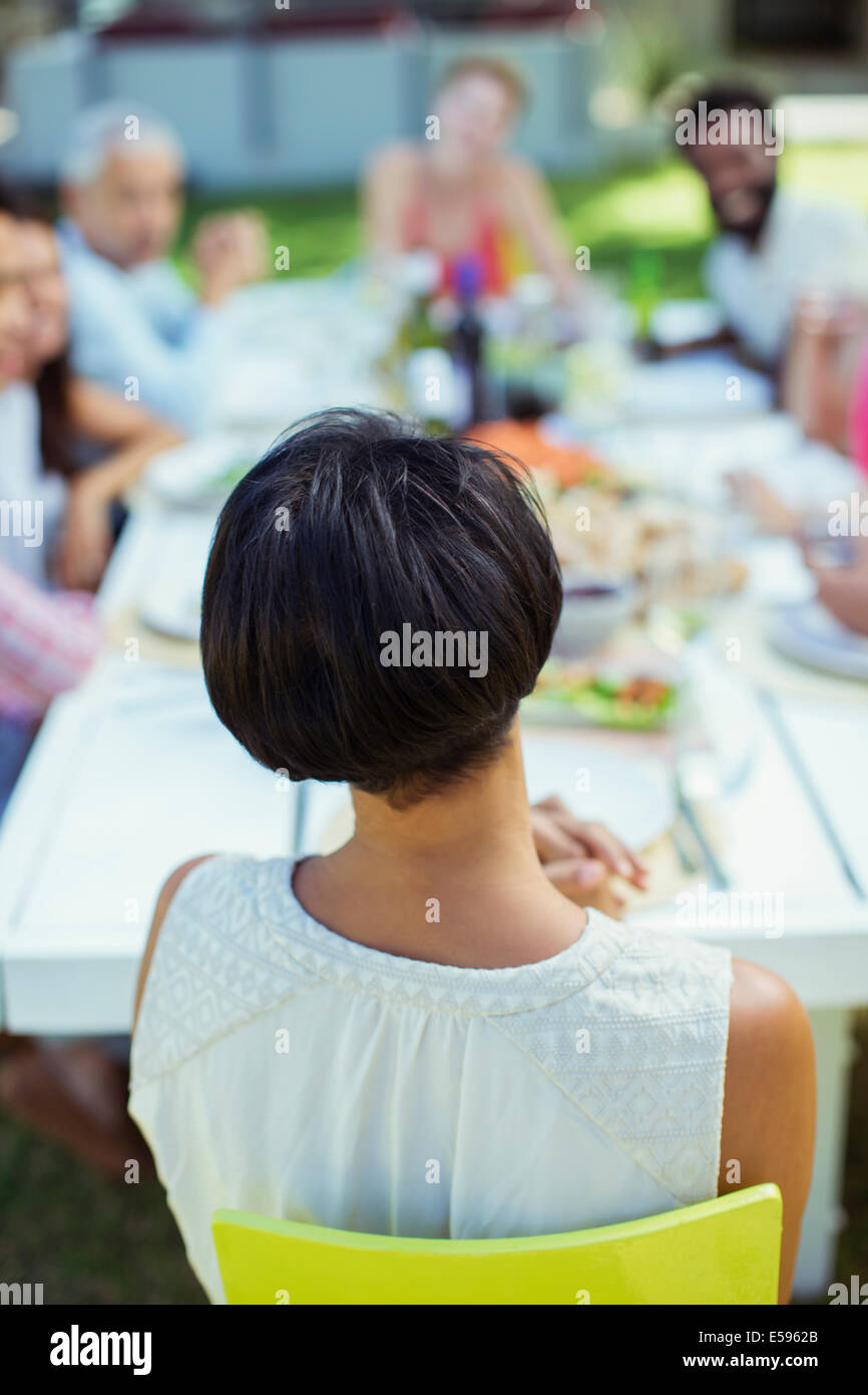 Woman sitting at table outdoors - Stock Image