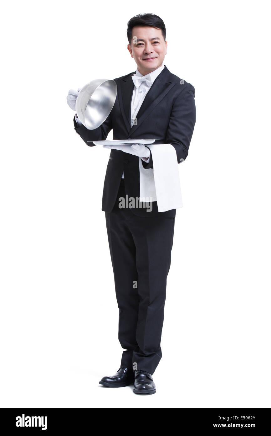 Happy waiter serving food - Stock Image