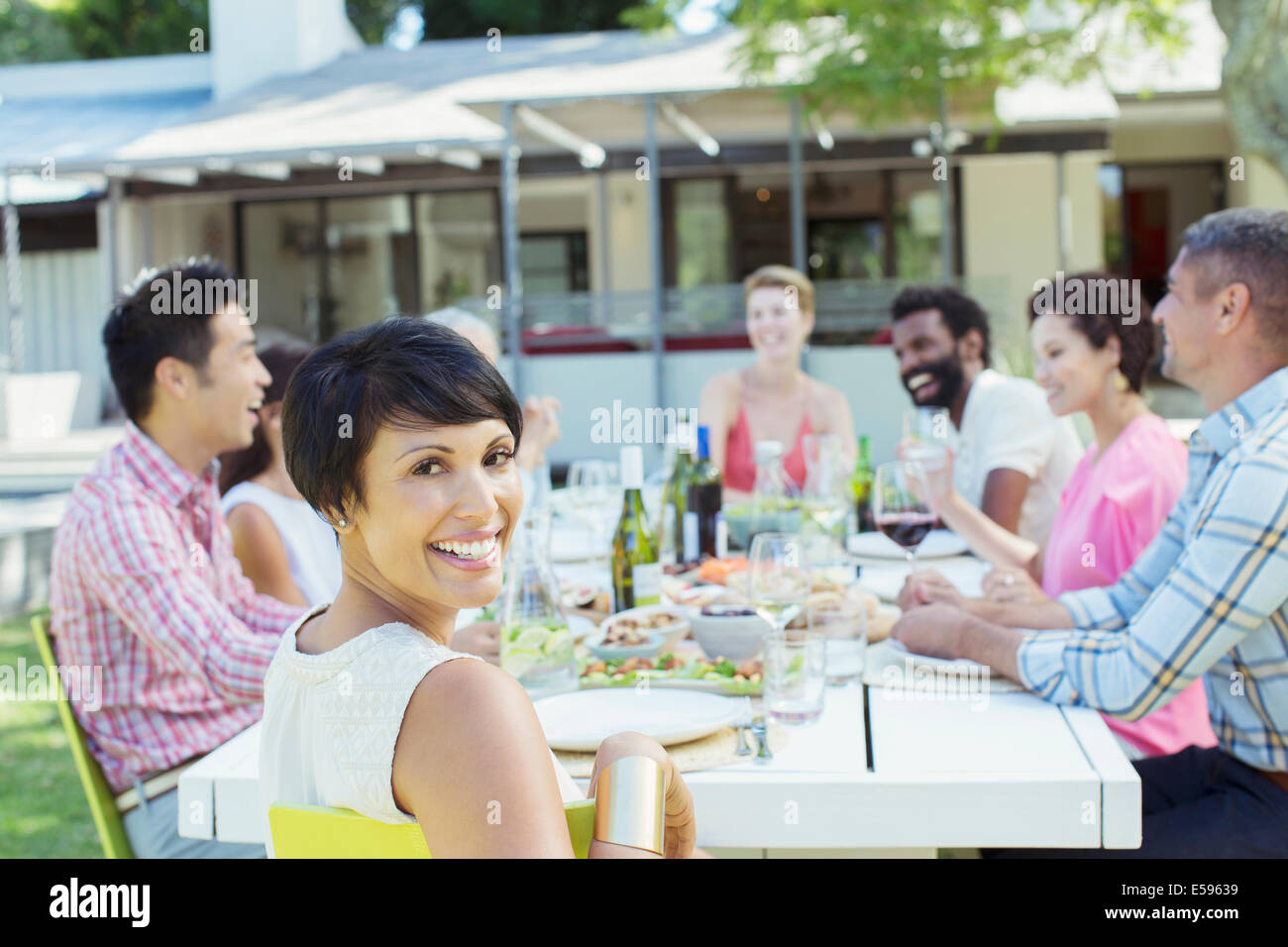 Woman smiling at table outdoors - Stock Image