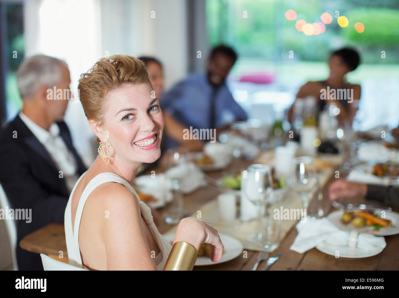 Woman smiling at dinner party - Stock Image
