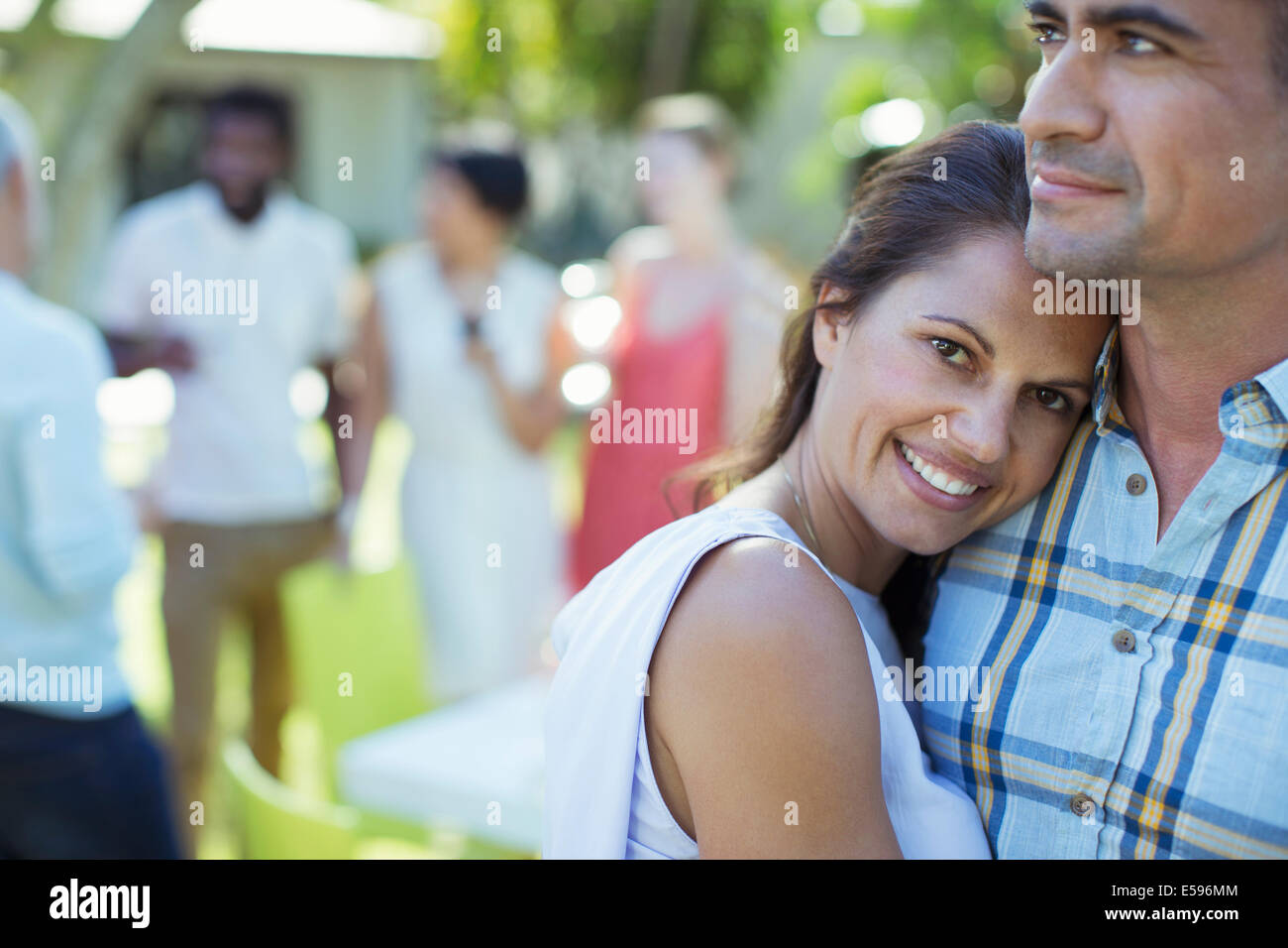 Couple hugging at dinner party - Stock Image