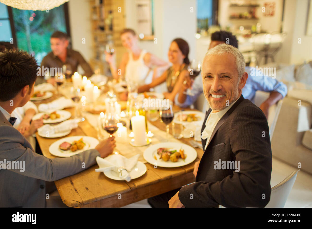 Man smiling at dinner party - Stock Image