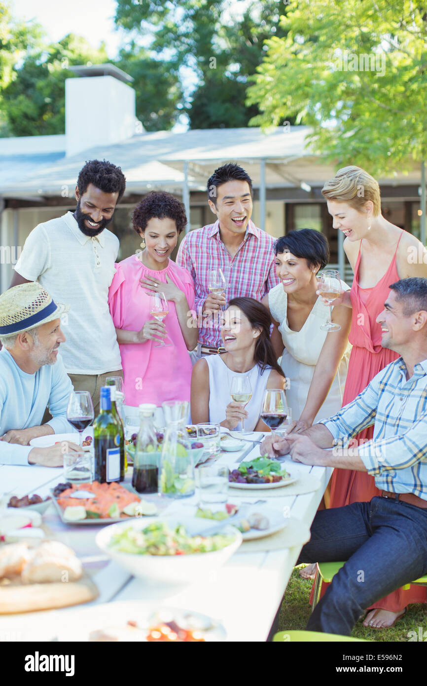 Friends relaxing together at table outdoors - Stock Image