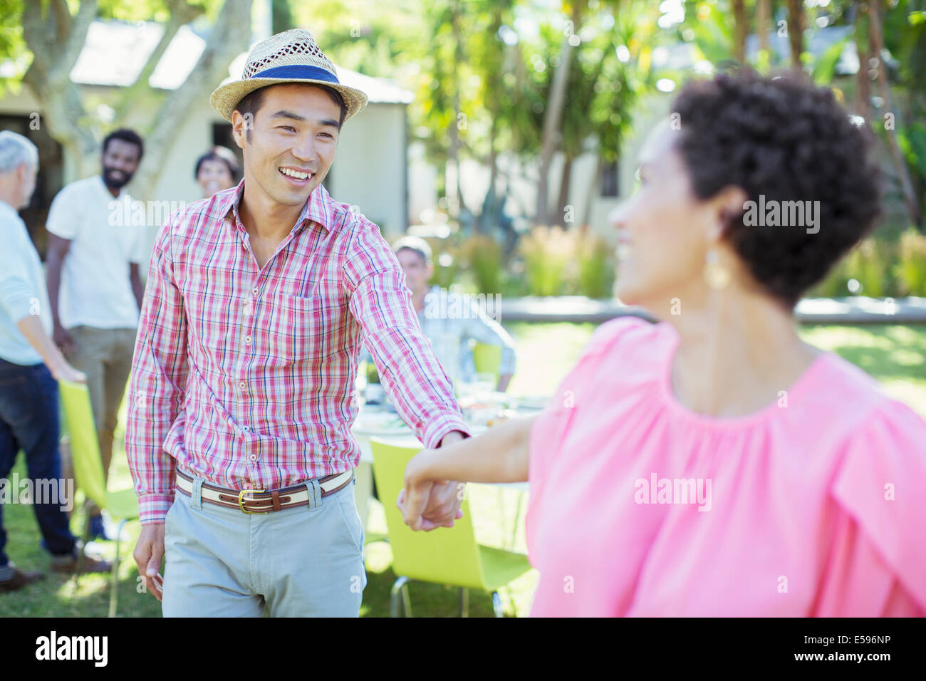 Couple holding hands at party - Stock Image