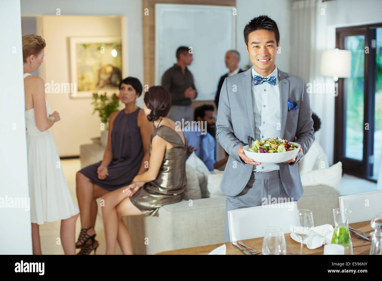 Man serving food at dinner party - Stock Image