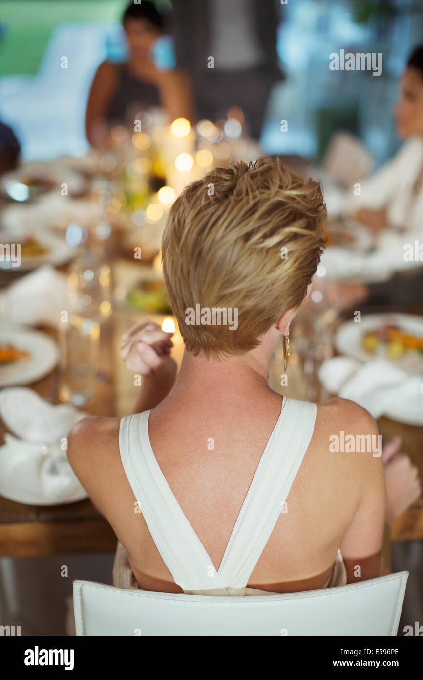 Woman sitting at dinner party - Stock Image