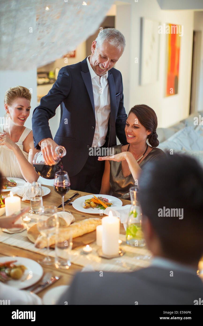 Man serving wine at dinner party - Stock Image
