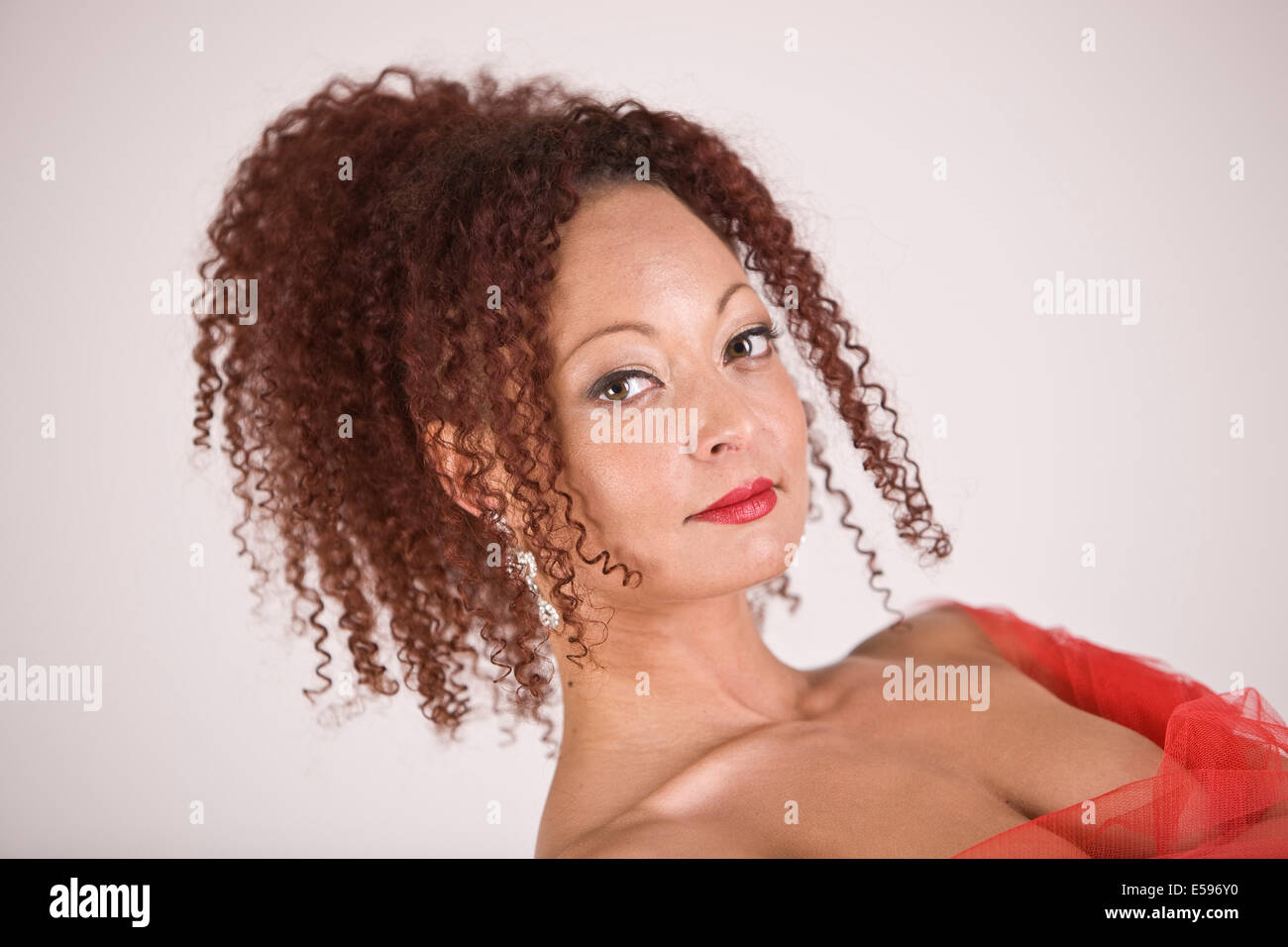 Lady with curly hair tied up showing her neck and shoulders - Stock Image