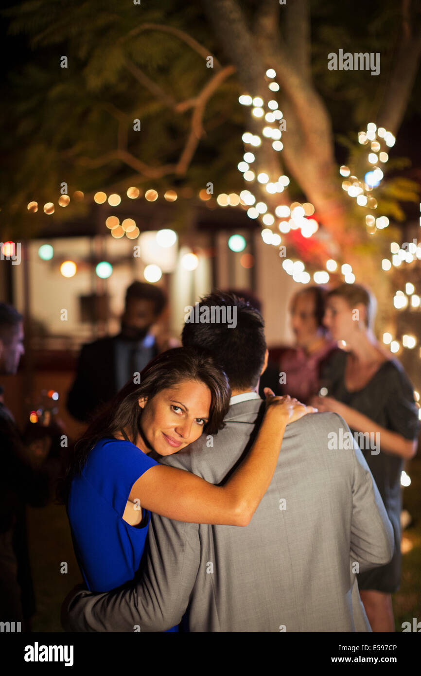 Couple hugging at party Stock Photo