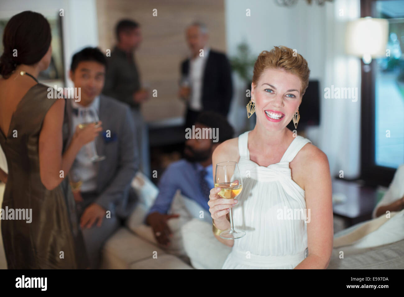 Woman smiling on sofa at party - Stock Image