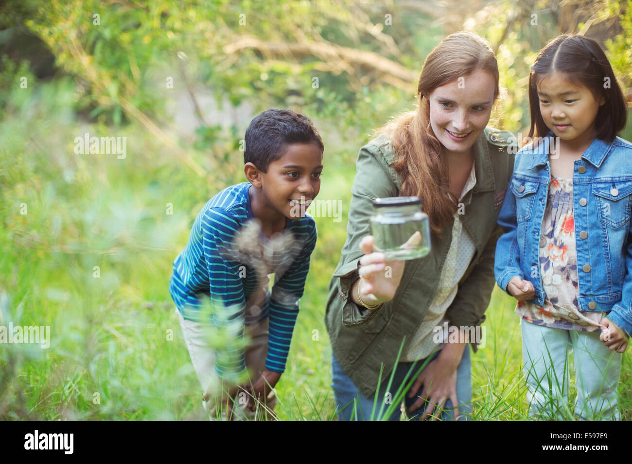 Student and teacher examining insect in jar - Stock Image